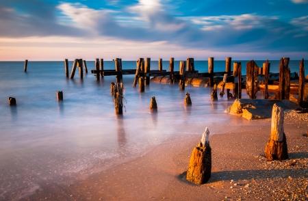Lange blootstelling bij zonsondergang van de pier palen in de Baai van Delaware op Sunset Beach, Cape May, New Jersey.