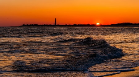 The Cape May Point Lighthouse and waves on the Atlantic at sunset, seen from Cape May, New Jersey. photo