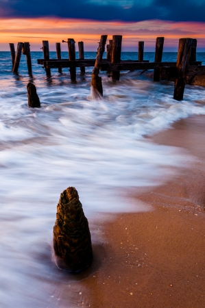 pilings: Waves swirl around pier pilings in the Delaware Bay at sunset, seen from Sunset Beach, Cape May, New Jersey.