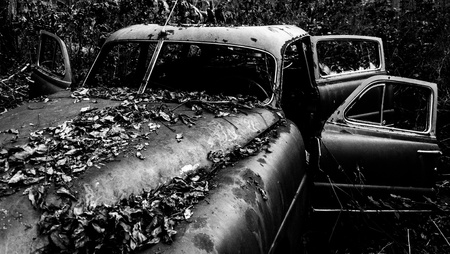 Black and white image of a rusty, abandoned car covered in fallen leaves, found in the woods. photo