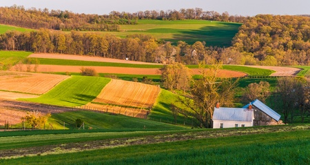 backroad: Home and barn on the farm fields and rolling hills of Southern York County, Pennsylvania. Stock Photo