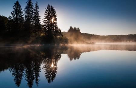 The sun shines through pine trees and fog at sunrise, at Spruce Knob Lake, Monongahela National Forest, West Virginia. Stock Photo - 20575468