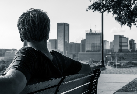 Man sitting on bench, looking toward the Baltimore Skyline from Federal Hill (black and white). Stock Photo