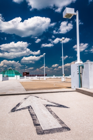 Arrow and street lamp under a partly cloudy sky, on top of a parking garage in Towson, Marylnd. Stockfoto