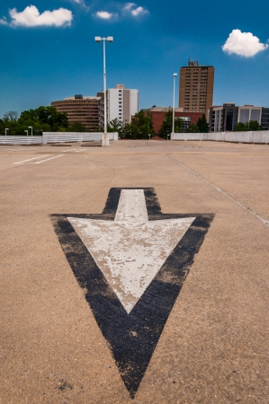 Arrow in parking lot and view of highrises from a parking garage in Towson, Maryland. photo