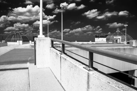 Black and white image looking up a parking garage ramp, under a blue summer sky in Towson, Maryland. photo