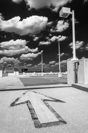 Black and white image of an arrow and street lamp under a partly cloudy sky, on top of a parking garage in Towson, Marylnd. photo