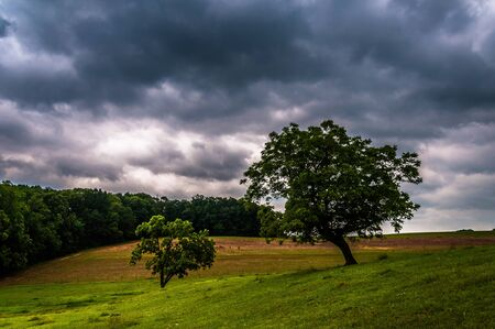 Dark stormy sky over trees and farm fields in York County, Pennsylvania. photo