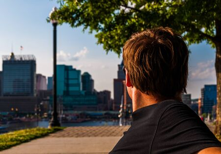 Man sitting on bench, looking toward the Baltimore Skyline from Federal Hill. photo