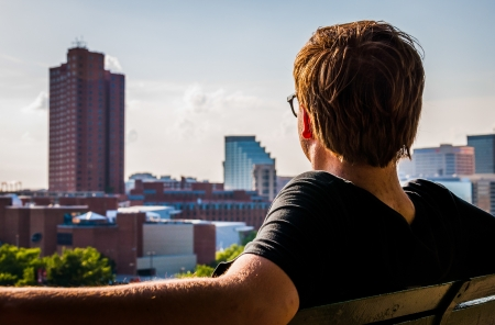 Man sitting on bench, looking toward the Baltimore Skyline from Federal Hill.