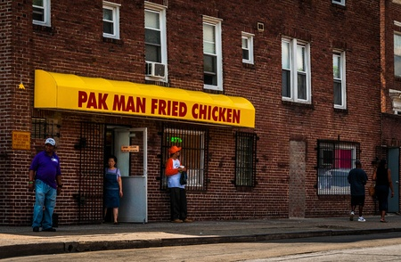bystanders: Pak Man Fried Chicken and people on the sidewalk, Baltimore, Maryland. Editorial