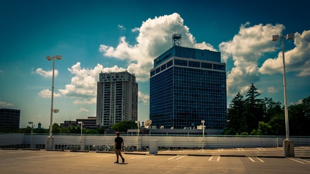 View of highrises and a man walking on a parking garage in Towson, Maryland.