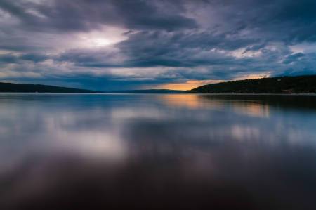 long lake: Storm clouds move over Lake Cayuga in a long exposure, seen from Stewart in Ithaca, New York. Stock Photo