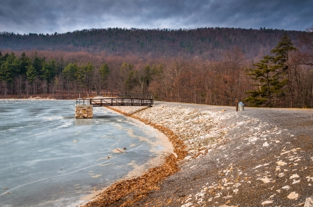 ice dam: Dark clouds over Cowans Gap Lake, seen frozen over during the winter.