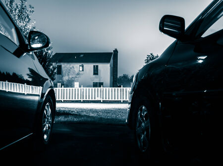 A house between two cars, at night. Stock Photo - 25009481