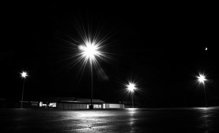 Bright lights in an empty parking lot at night. Imagens
