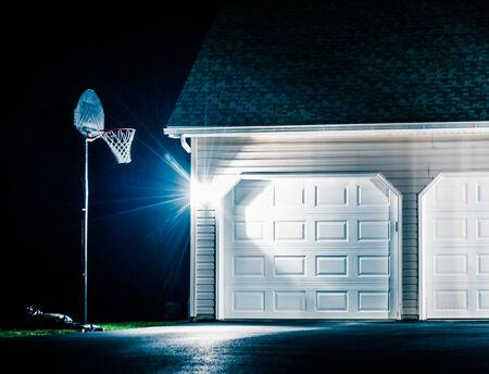 Garage and basketball hoop at night. photo