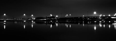 Lights and highways reflecting in the Potomac River at night, seen from National Harbor, Maryland. photo