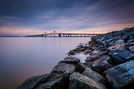 Long exposure of a jetty and the Chesapeake Bay Bridge, from Sandy Point State Park, Maryland. Stock Photo