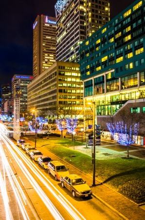 Long exposure of traffic moving past modern buildings on Pratt Street at night in Baltimore, Maryland.