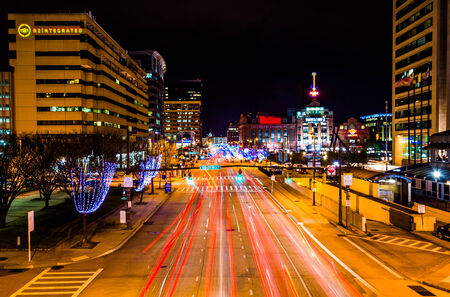 Long exposure of traffic moving past modern on Pratt Street at night in the Inner Harbor of Baltimore, Maryland.