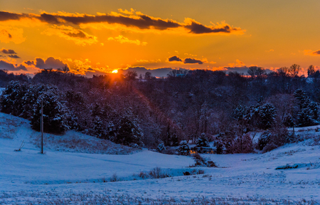 covered fields: Sunset over snow covered fields and trees in rural York County, Pennsylvania.