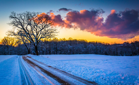 winter road: Sunset over trees and a snow covered field along a dirt road in rural York County, Pennsylvania. Stock Photo
