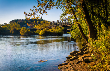 west virginia trees: Trees and train bridge over the Potomac River in Harpers Ferry, West Virginia.