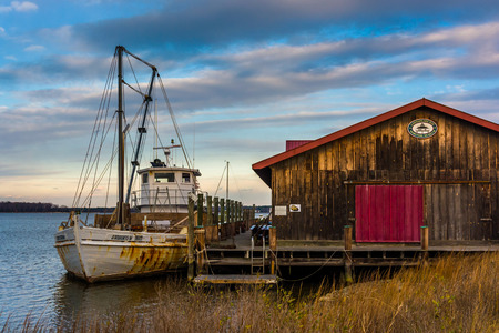 Boat and old building on the shore of the Chesapeake Bay, in St. Michaels, Maryland.