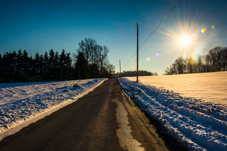 Sun over a country road through snow-covered fields in rural York County, Pennsylvania. Archivio Fotografico