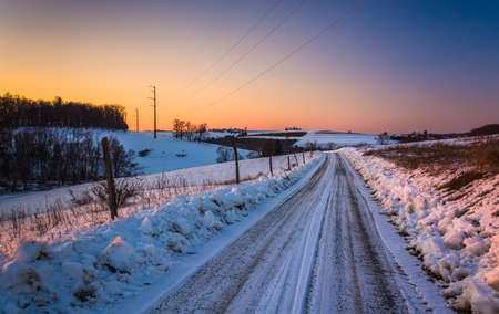 Sunset over a snow-covered dirt road in rural York County, Pennsylvania. photo