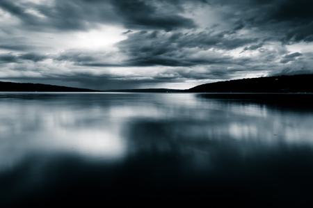 water's edge: Storm clouds move over Lake Cayuga in a long exposure, seen from Stewart in Ithaca, New York. Stock Photo