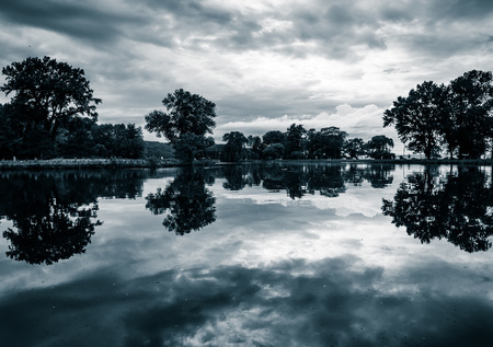 stormy waters: Storm clouds reflect in a pond at Stewart Park in Ithaca, New York. Stock Photo