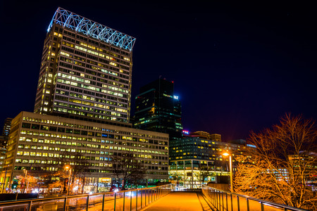 Elevated walkway and modern skyscrapers at night in Baltimore, Maryland.