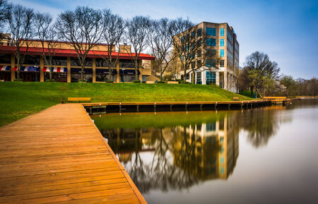 Long exposure of a walkway and buildings along the shore of Lake Kittamaqundi, in Columbia, Maryland. Editorial