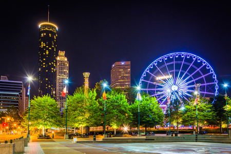 観覧車と、ジョージア州アトランタで夜にセンテニアル ・ オリンピック公園から見られる建物です。