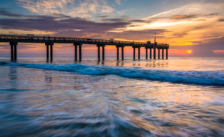 Wellen auf den Atlantischen Ozean und Fischerei Pier bei Sonnenaufgang, St. Augustine Beach, Florida.
