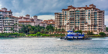 Boat in Biscayne Bay and buildings on Fisher Island, seen from South Beach, Miami, Florida. Editorial
