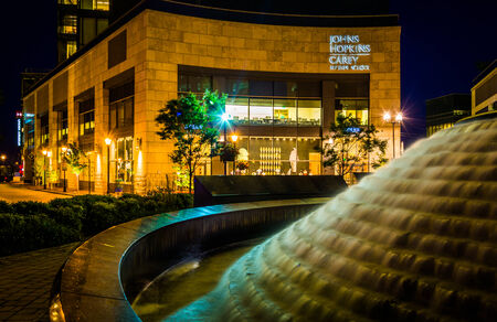 Fountain and the John Hopkins Carey Business School at night in Harbor East, Baltimore, Maryland.