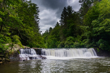 Dark clouds over Hooker Falls on the Little River in Dupont State Forest, North Carolina. Stock Photo