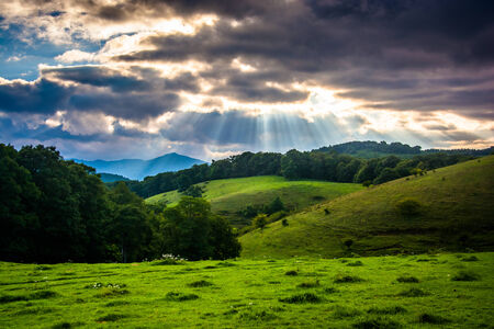 crepuscular: Crepuscular rays over  a field and rolling hills at Moses Cone Park on the Blue Ridge Parkway in North Carolina.