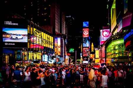 Large crowd of people in Times Square at night, in Midtown Manhattan, New York.