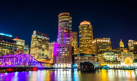 boston: The Boston skyline and Fort Point Channel at night from Fan Pier Park, Boston, Massachusetts.