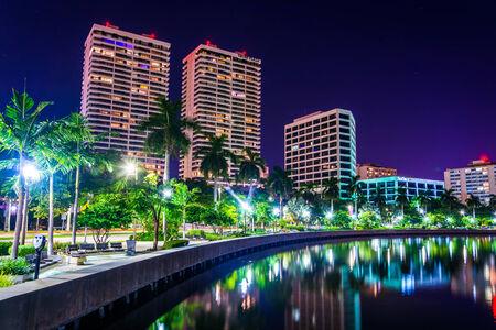 Palmbomen langs de Intracoastal Waterweg en de skyline in de nacht in West Palm Beach, Florida. Redactioneel