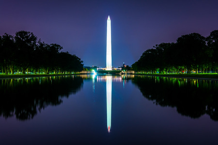 The Washington Monument reflecting in the Reflection Pool at night at the National Mall in Washington, DC.