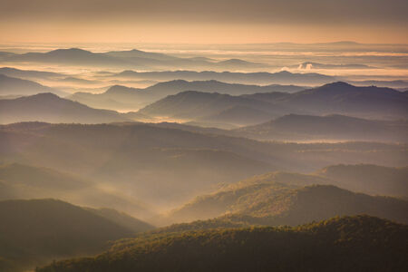 Sun shining through fog in the valley, seen from Beacon Heights, along the Blue Ridge Parkway near Blowing Rock, North Carolina. 版權商用圖片