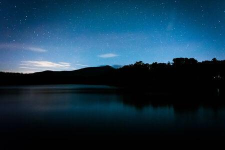 julian: Stars over Julian Price Lake at night, along the Blue Ridge Parkway in North Carolina. Stock Photo