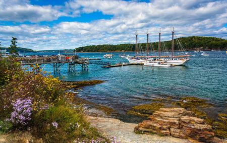 barra: Costa rocosa y vista de los barcos en el puerto de Bar Harbor, Maine.