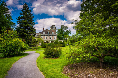 arboretum: Bushes and trees along a path and the Cylburn Mansion at Cylburn Arboretum, Baltimore, Maryland.