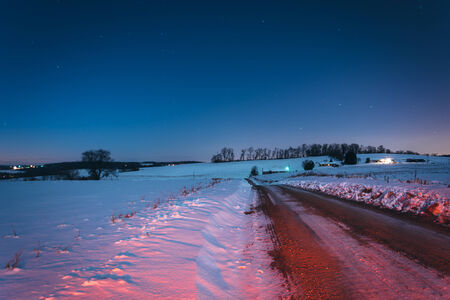 covered fields: Snow covered fields along a dirt road at night, in rural York County, Pennsylvania. Stock Photo